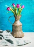 De lente purpere tulpen in uitstekende rustieke koperkruik, blauwe muur Royalty-vrije Stock Afbeeldingen