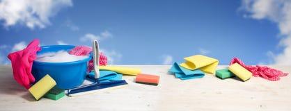 De lente schoonmakende banner, blauwe plastic kom met zeepschuim, roze r stock afbeeldingen