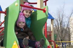 In de lente van twee meisjes die op de speelplaats spelen Stock Fotografie