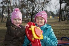 In de lente van twee meisjes die op de speelplaats spelen Stock Afbeelding