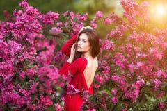 De lenteaanraking De gelukkige mooie jonge vrouw in rode kleding geniet van verse roze bloemen en zonlicht in bloesempark bij zon Royalty-vrije Stock Fotografie