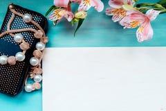 De lenteachtergrond van houten raadslay-out in entrepot op een blauwe houten achtergrond met de beurs en de parels van het bloeme Stock Foto's