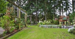De lentebinnenplaats van het huis met rozenterras en jonge geitjesspeelplaats. Stock Afbeeldingen