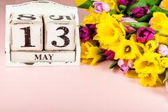 De lentebloemen en Houten Blokken met de Datum van de Moedersdag, 13 Mei, Stock Afbeelding
