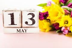 De lentebloemen en Houten Blokken met de Datum van de Moedersdag, 13 Mei, Stock Foto's