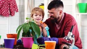 De lenteconcept, aard en zorg De leuke kindjongen helpt zijn vader om voor installaties te geven Installatiebloemen Mens met een  stock video