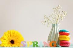 De lentedocument woord met gele bloem en macfroons op achtergrond Hello-de Lente De lentebehang Stock Foto