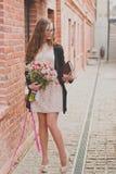 De lentegang van een meisje met een bloemboeket stock foto