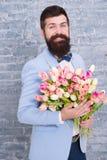 De lentegift Gebaarde mens hipster met bloemen Gebaarde mens met tulpenboeket Bloem voor 8 Maart De datum van de liefde royalty-vrije stock foto