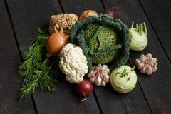 De lentegroenten op een donkere achtergrond: Savooiekool, bloemkool, ui, knoflook, koolraap, selderiewortel, dille Royalty-vrije Stock Foto's