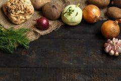 De lentegroenten op een donkere achtergrond: ui, knoflook, koolraap, selderiewortel, dille, bieten, aardappels Royalty-vrije Stock Foto's