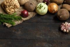 De lentegroenten op een donkere achtergrond: ui, knoflook, koolraap, selderiewortel, dille, bieten, aardappels Stock Foto