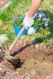 De lentehuis die, het schoffelen grond en het planten van bloemen tuinieren Royalty-vrije Stock Afbeeldingen