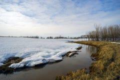 De lentelandschap met een beek achter sneeuwhoop Stock Foto's