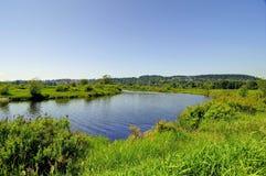 De lentelandschap met rivier en weide Royalty-vrije Stock Afbeeldingen