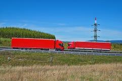 De lentelandschap met weg en tegemoetkomende rode vrachtwagens die rond pyloon overgaan Royalty-vrije Stock Foto