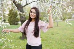 De lentemeisje die als achtergrond van geur in een bloeiende tuin genieten De ruimte van het exemplaar Gelukkige jonge vrouw stock afbeelding