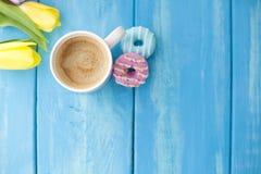 De lenteochtend, geurige koffie en tulpen van gele en roze kleur Donuttsyexemplaren Blauwe houten achtergrond, plaats voor tekst  royalty-vrije stock foto's