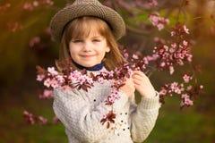 De lenteportret, aanbiddelijk meisje in hoedengang in de tuin van de bloesemboom op zonsondergang royalty-vrije stock foto's