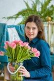 De lenteportret van een meisje met roze tulpen stock afbeelding