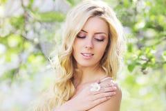 De lenteportret van een mooie vrouw die in het bloeien genieten van stock afbeeldingen