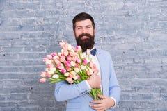 De lentestijl De dag van vrouwen is op 8 maart De lentegift Gebaarde mens hipster met bloemen De datum van de liefde Internationa stock fotografie