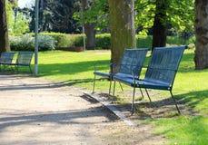 De lentetijd in park met blauwe bank Stock Fotografie