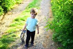 De lentevakantie zonnig weer Klein kind met stuk speelgoed in het winkelen zak De zomer Weinig jongenskind in groen bos Gelukkig  stock afbeeldingen
