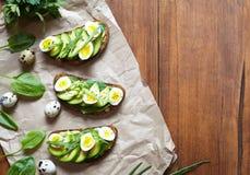De lentevoedsel Een gehele de toostsandwich van het korrelbrood met avocado, spinazie, guacamole en kwartelseieren op perkament Royalty-vrije Stock Foto
