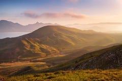 De lentezonsondergang in de bergen Zeekust en heuvels stock fotografie