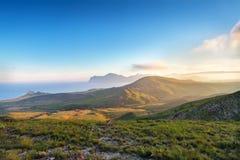 De lentezonsondergang in de bergen Zeekust en heuvels stock foto's