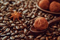 De lepel van donkere chocolade met de eigengemaakte gezonde truffels van de veganistchocolade wordt gemaakt ligt op de koffiebone Royalty-vrije Stock Afbeelding