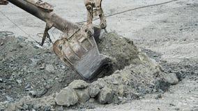 De lepel van graafwerktuig graaft gat Het graafwerktuig graaft kuil in reden tot bouw of mijnbouw Mijnbouw en steengroevemateriaa stock foto
