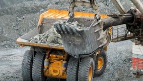 De lepel van graafwerktuig graaft gat Het graafwerktuig graaft kuil in reden tot bouw of mijnbouw Mijnbouw en steengroevemateriaa stock foto's