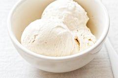 De lepels van het vanilleroomijs in witte kom Stock Foto's