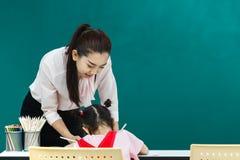 De leraar besteedt aandacht bij meisje stock foto