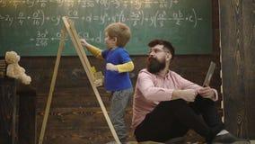 De leraar controleert student het schrijven op bord Leerling die aan zijn privé-leraar of papa spreken terwijl het oplossen van t stock videobeelden