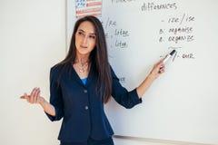 De leraar dichtbij whiteboard verklaart de regels Leer vreemde taal royalty-vrije stock afbeeldingen