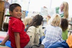 De leraar die van de kleuterschool aan kinderen leest Stock Foto