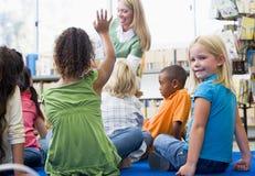 De leraar die van de kleuterschool aan kinderen leest
