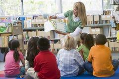De leraar die van de kleuterschool aan kinderen leest Stock Foto's