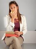 De leraar eet appel bij bureau Stock Afbeeldingen