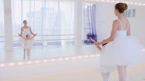 De leraar en het meisje leiden balletstappen dichtbij de spiegel op dansklasse op stock footage