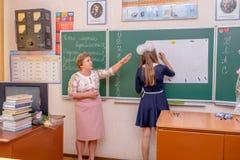 De leraar en het schoolmeisje van de lage school dichtbij chalkboar stock afbeelding