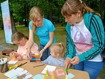 De leraar geeft aan de kindplasticine voor beroep Kinderen` s hoofdklasse in openlucht stock afbeelding