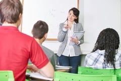 De leraar geeft een klasse en wijst op met haar vinger Stock Afbeeldingen