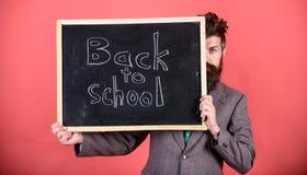 De leraar of het schoolhoofd heten terug naar school welkom Bent u klaar studie Het verbergen van de leraar achter bord prepare stock fotografie