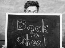 De leraar of het schoolhoofd stemmen in met inschrijving terug naar school Leraars die uit bord gluren Opvoeder die erachter verb royalty-vrije stock fotografie