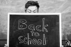 De leraar of het schoolhoofd stemmen in met inschrijving terug naar school Leraars die uit bord gluren Opvoeder die erachter verb stock foto's