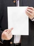 De leraar houdt leeg blad van document in handen Stock Afbeelding
